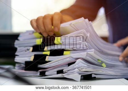 Stacks Documents Of Paper Files, Businessman Hands Working In Messy Bureaucracy And Searching Inform