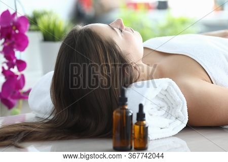 Girl Lying At Home Under Towel After Massage. Cosmetic Procedures During Quarantine Using Organic Oi