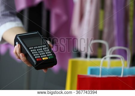 Hand Holds Out Terminal For Credit Card Payment. Simple And Easy To Manage Finances On Credit Card.