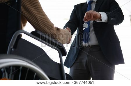 Man In Suit Passes House Keys To Disabled Person. Application For Benefits And Services. Financial A