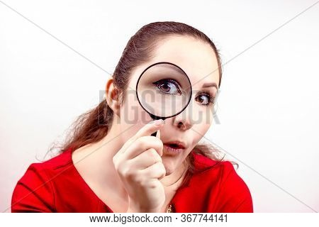 Young Attractive Woman With Magnifying Glass In Her Hand Near The Eye. Inspection, Discovery, Resear