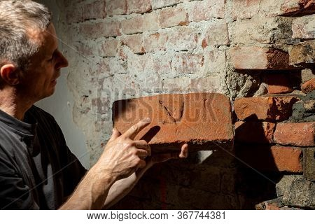 Man Worker Reconstructing Old Stone Wall. Old House Reconstruction, Repair