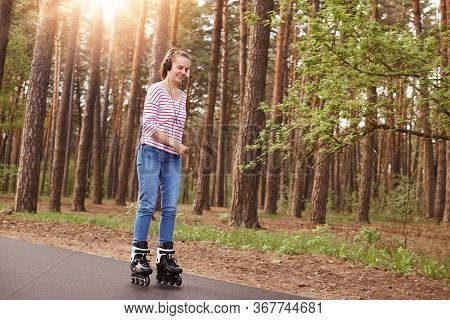 Image Of Cheerful Attractive Sweet Young Female Rollerskating Breathing Fresh Air, Wearing Casual Cl