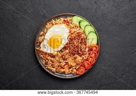Nasi Goreng - Indonesian Chicken Fried Rice On Black Plate On Dark Slate Backdrop. Nasi Goreng Is An