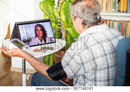 telemedicine concept elderly man in an online consultation taking his blood pressure at home