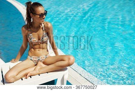 Beautiful Sexy Woman In Bikini Swimsuit And Sunglasses Sunbathing Near Swimming Pool.