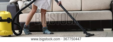 Woman With Mask On Her Face Vacuuming Carpet. Flooring Must Be Cleaned Regularly. In Everyday Condit