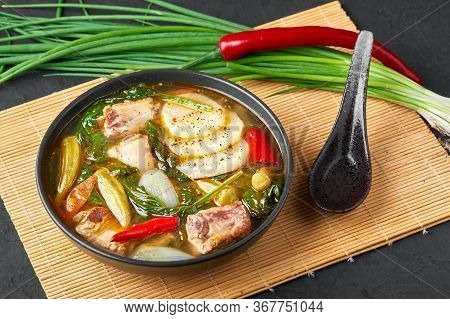 Sinigang Na Baboy Or Filipino Pork Meat Soup In Black Bowl On Dark Slate Backdrop. Sinigang Is A Fil