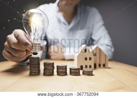Businessman Holding And Putting Lightbulb To Coins Stacking. Creative New Business Idea Can Make Pro