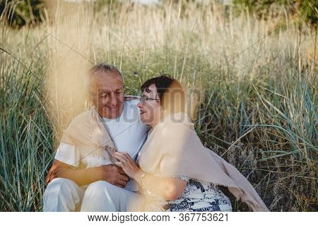 An Old Married Couple On A Summer Walk In The Field. The Couple Sit Hugging Each Other In The Grass