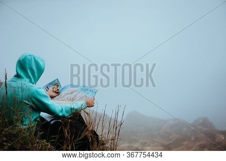 Traveler With A Map Sitting On The Hill Of A Mountain In Front Of A Gorgeous Panorama View To The Va