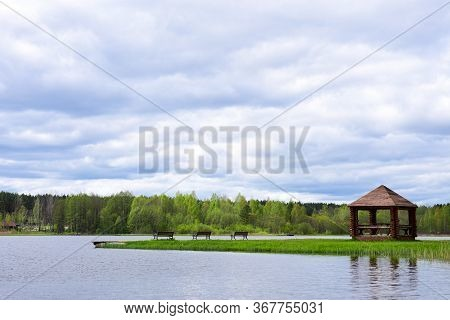 Picnic Arbor With Benches On The Shore Of A Forest Lake.