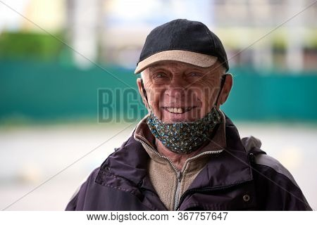 Kiev, Ukraine, 20.05.2020: The Old Grandfather, Wearing A Medical Mask, Wearing A Cap, Smiles And Lo