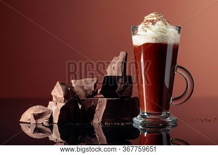 Hot Chocolate With Whipped Cream And Pieces Of Dark Chocolate On A Brown Background. Copy Space.