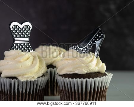 Chocolate Cupcakes With White Swirled Frosting Decorated With A Black And Silver Polka Dot Dress And