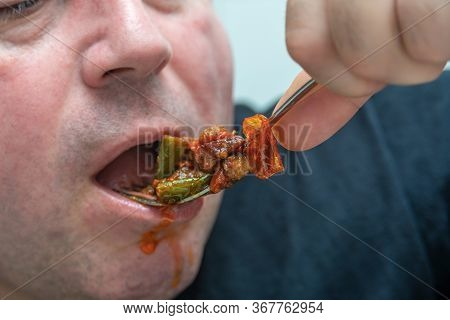 A Hungry And Fat Fat Man Eagerly Eats Roasted Meat With Spices, Fat From His Mouth Flows Through His