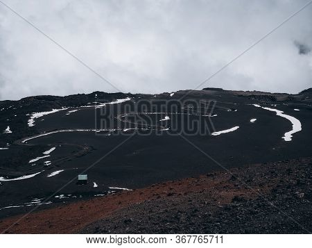 The Slope Of Mount Etna Covered With Dried Lava, Snow And Clouds Above It