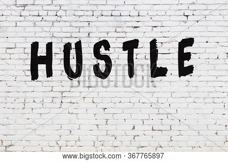 Word Hustle Written With Black Paint On White Brick Wall.