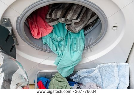 White Front-loading Washing Machine, Full Of Clothes. Cleaning Laundry. Dirty Laundry In The Washing
