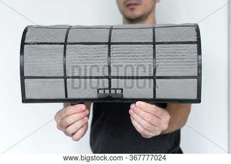 The Guy Cleans The Filter Of The Home Air Conditioner From Dust. Very Dirty Air Conditioner Filter.