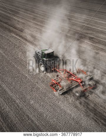 Aerial View Of A Clean Field In Which The Tractor Makes Vertical Tillage. Red Tillage Equipment And
