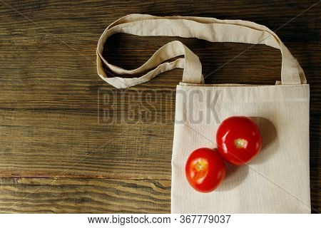 Eco Bag And Two Red Tomatoes On A Wooden Background. Eco Bag Of Cotton On Brown Wooden Background. Z