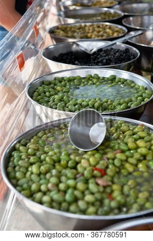 Different pickled olives in brine in outdoor market. Traditional spanish food. Snack