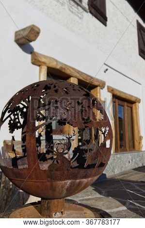 Globe-shaped Wrought Iron Sculpture Depicting A Mountain Scene With Deer Outside A Chalet In The Ita