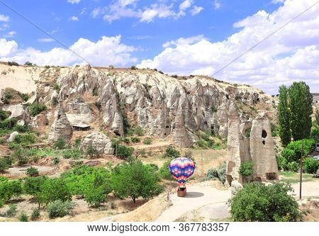 Small decorative balloon and caves in medieval open air Christian monastery complex Goreme, Cappadocia, Turkey. UNESCO world heritage site