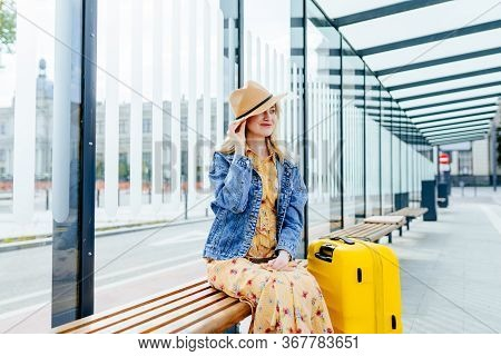 Blond Positive Smiling Woman Traveler In Straw Hat, Denim Jacket, Summer Dress Leans And Looks Down