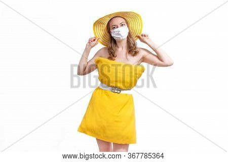 Woman In A Yellow Pillow Dress And Hat Wearing A Protective Medical Mask On A Isolated White Backgro