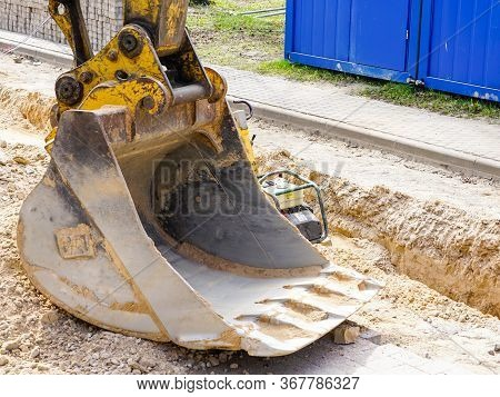 Excavator Bucket At The Construction Site Near The Excavated Trench