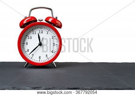 Vintage Red Alarm Clock On Dark Slate Plate Isolated On White Background. Copy Space On The Right.