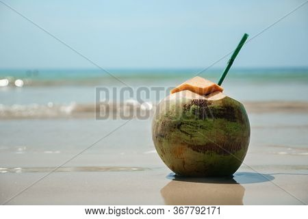 Delicious Fresh Coconut With Chopped Top And Straw Stands On Wet Beach Sand Against Magnificent Blur