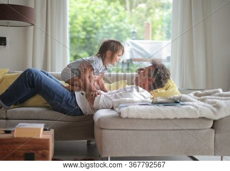 father plays with his daughter on the sofa