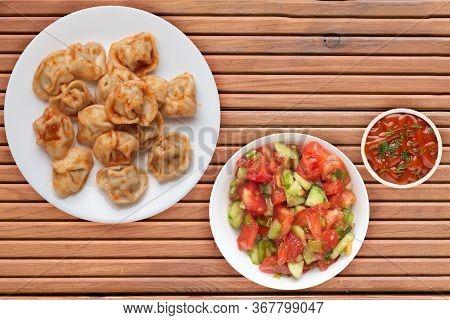 Dumplings On A White Plate On Orange Wooden Background. Dumplings In Tomato Sauce With Salad. Dumpli