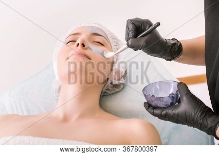 Process Of Applying A Silver Cosmetic Mask With Brush To Female Client Head Skin, On A White Backgro