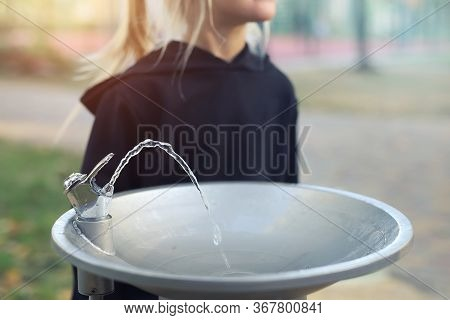 Cute Adorable Caucasian Blond Little Thirsty School Girl Drinking Water From Public Potable Fountain