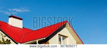 Roof Of A House Or Cottage Made Of Red Metal Tiles With Drains, Slopes, Tides, Chimney Against The B