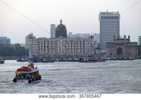 MUMBAI, INDIA - FEBRUARY 15, 2020: Taj Mahal hotel, Gateway of India and tourist boats in water of Arabian Sea in Mumbai, India