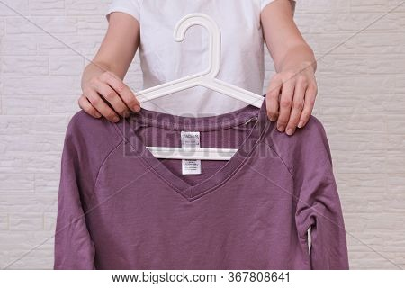 Caucasian Woman Choosing Clothes, She Is Holding A Hanger With Lilac Longsleeve , Shopping, Fitting