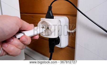 Overloaded Outlet With An Extension And Many Sockets Plugged In, A Hand Plugging A Socket Into The O
