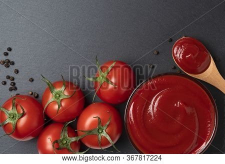 Ketchup And Multiple Tomatoes Placed On Black Stone Background