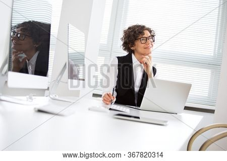 Portrait of a pretty business woman dreaming at workplace in office