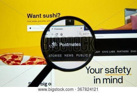 Montreal, Canada - May 2, 2020: Postmates Official Website Under Magnifying Glass. Postmates Is An A