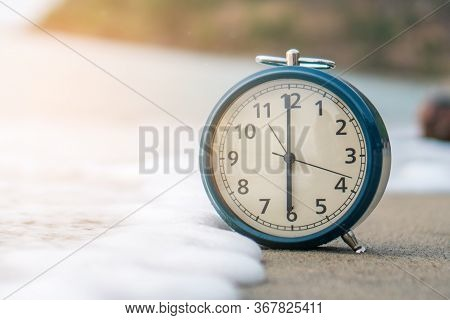 Selective Focus Of Alarm Clock On Side Table Beside Bed Show 6 O'clock In The Morning Background.tim