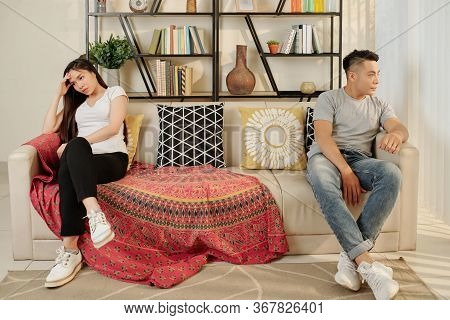Asian Boyfriend And Girlfriend Sitting On Both Sides Of Sofa After Having Argument