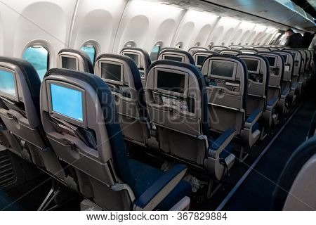 The Interior Of The Aircraft. Empty Airplane Cabin. Rows Of Passenger Seats With Screens In The Head