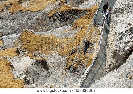 Lauterbrunnen, Switzerland - October 2019: Tourists Walking On The Thrill Walk, The Cliff Pathway Do
