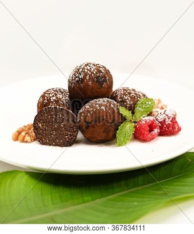 Chocolate Balls Made From Cocoa And Walnuts With Condensed Milk, Cakes On A White Plate With Raspber